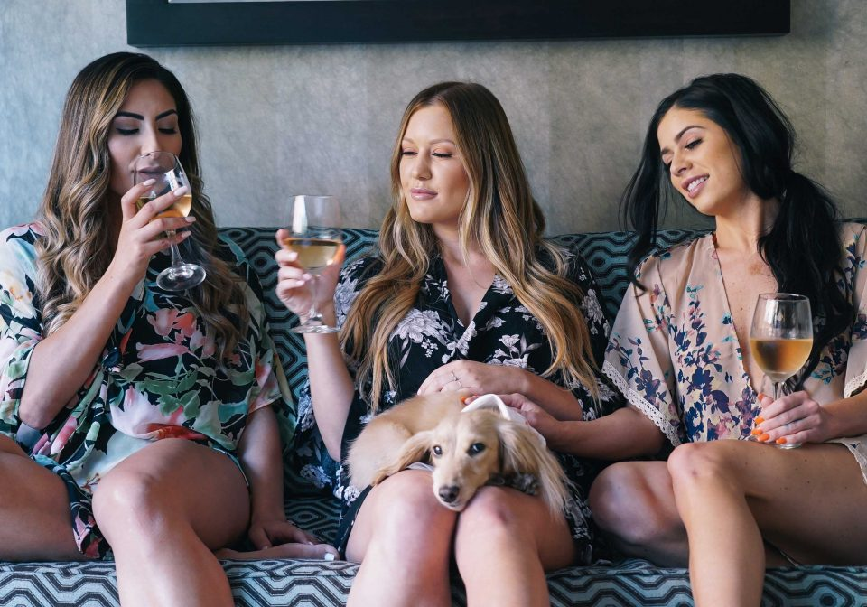 Three women drink wine on a couch