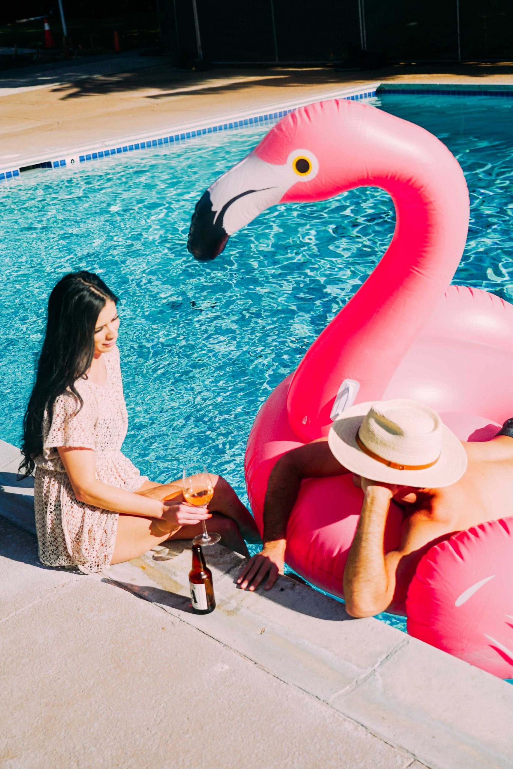 Two women sitting in a flamingo floatie in the pool